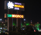 The illuminated sign of 5M Migros at night