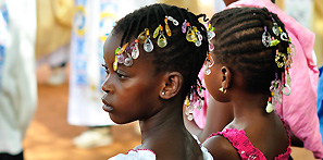 Cute girls are on the Sunday service in the yard of Cathedral of St. John the Baptist in Korhogo