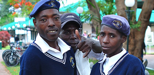 Two law enforcement officers with a local man are on a street in the town of Victoria Falls, Zimbabwe